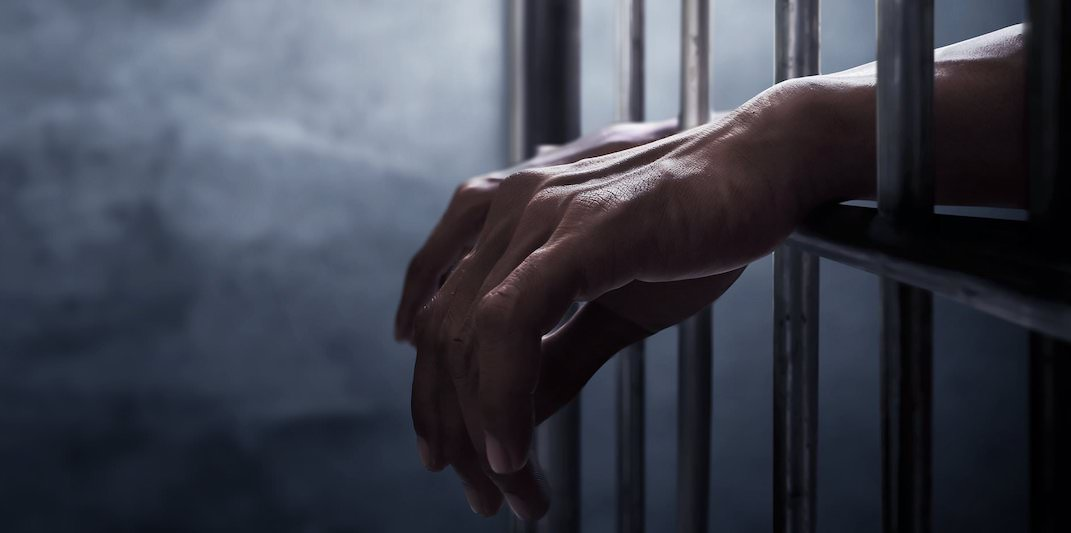 Руки, высунутые из-за тюремной решетки
